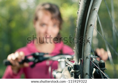 close up - mountain bike wheel with an attractive young woman in ...