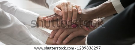 Close up multiracial business people stack holds their hands together as symbol gesture concept of unity togetherness assistance and support horizontal panoramic photo banner for website header design #1289836297