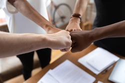 Close up multiracial colleagues bumping fists at meeting. Young mixed race employees engaged in motivating teambuilding process at office. Group of different ethnicities business people showing unity.
