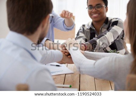 Close up multiracial group of young millennial businesspeople or students stacking their hands palm, sitting in office work meeting. Gesture symbol of support unity, starting common business concept