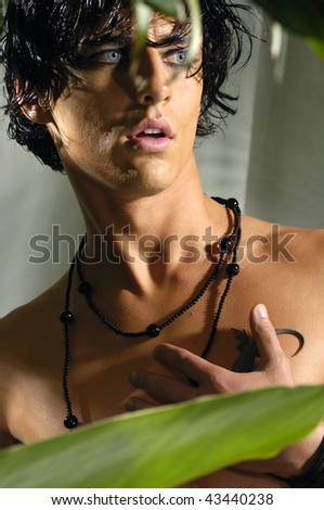 Close up muscular man posing with green leaf