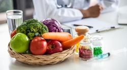 Close up, natural fresh fruits, apple, broccoli, carrot, vegetables and multivitamins in the basket on the table. Blurred background is a doctor or nutritionist advising about healthy lifestyles