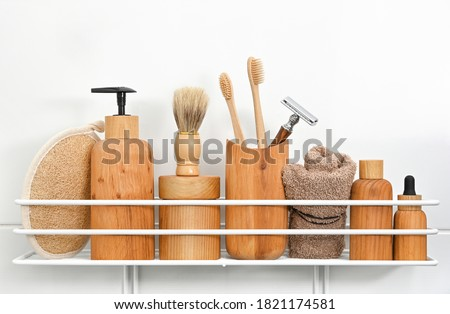 Close up natural wooden bottles of cosmetic beauty care products, towels, hygiene and grooming accessories on bath shelf over white background, low angle view Stockfoto ©