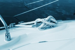Close-up nautical knot rope tied around stake on boat or ship, boat mooring rope.