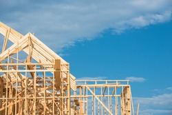Close-up new stick built home under construction under blue sky in Humble, Texas, US. Framing structure/wood frame of wooden houses/home. House construction and real estate concept background.