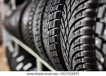 close-up new tires in the auto repair service center, brand new winter tires with a modern tread isolated. selective focus. tire stack background.winter season, no people