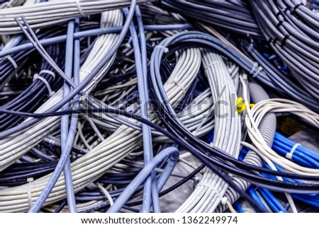Close up not packed tangled wires abstract background. Untidy coil of lan, power, network, optic and telephone cables in datacenter. Cabling mess in server room #1362249974