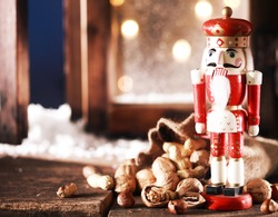 Close up Nutcracker Toy and Nuts on Wooden Table Near Window Pane. Captured on Christmas Holiday Season.