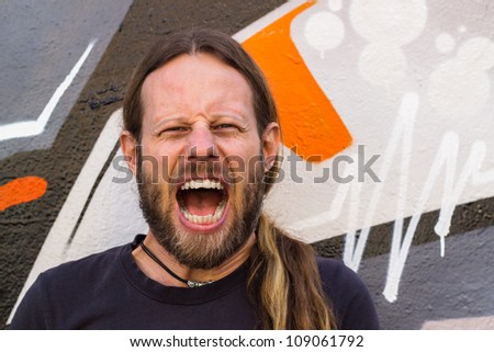 Close-up of a angry, screaming man against a graffiti wall.