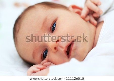 Close up of a baby girl\'s face who is holding her arms close to her face. She is dressed in white and also background is white.