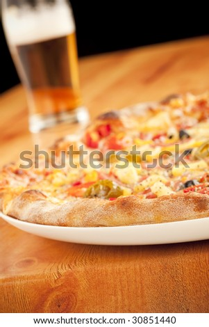 Close up of a baked pizza with pint of beer
