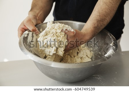 close up of a baker kneading...