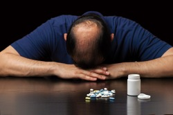 Close up of a bald man depressed by the ineffectiveness of pills to prevent hair loss on a dark background