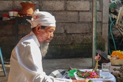 Close up of a Balinese pedanda during prayer. side view of a hindu priest performing a ceremony. A hindu priest performing offerings in a temple in Pemuteran in Bali, Indonesia.
