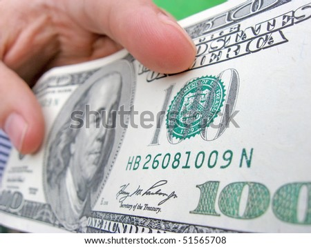 stock-photo-close-up-of-a-banknote-of-hundred-dollars-in-the-hand-51565708.jpg