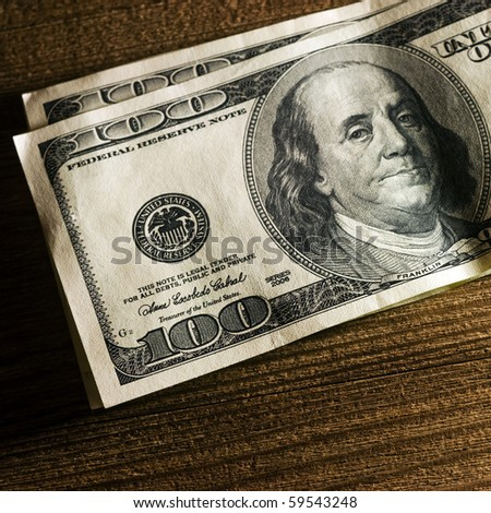 Close-up of a $100 banknotes on wooden background