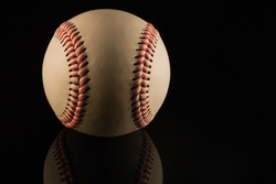 Close up of a baseball ball on black background with reflection