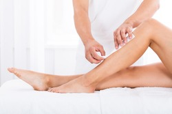 Close-up Of A Beautician Waxing Woman's Leg In Beauty Spa