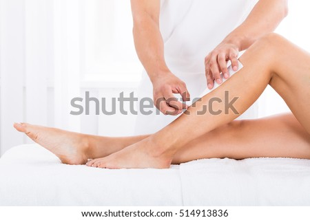 Close-up Of A Beautician Waxing Woman\'s Leg In Beauty Spa