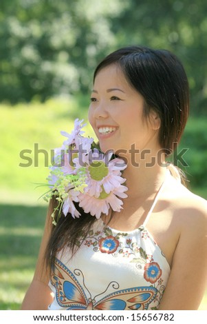 Close up of a beautiful Asian female with a bunch of flowers in a summer time, park setting