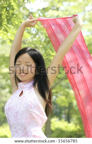 Close up of a beautiful Asian female with a scarf in a summer time, park setting