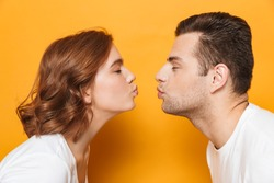 Close up of a beautiful couple wearing white t-shirts standing isolated over yellow background, kissing