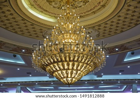 Close-up of a beautiful crystal chandelier . Gilded chandelier with burning candles in the Church. Large crystal chandelier in baroque style