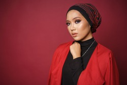 Close up of a beautiful female model wearing black shirt and red blazer with turban style hijab, isolated over red background. Muslim female fashion lifestyle portraiture concept.