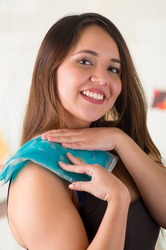 Close up of a beautiful smiling woman holding ice gel pack on her shoulder, medical concept, in office background