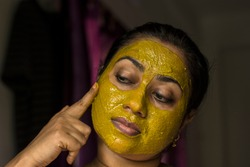 Close up of a beautiful woman with cosmetic facial green mask treatment all over her face.