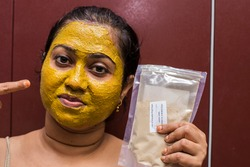Close up of a beautiful woman with cosmetic facial green mask treatment all over her face and the packet of mask holding with her hand..