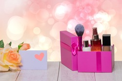 Close-up of a beautiful yellow blossom of flower and a empty tag with a pink heart on it and a purple gift box with cosmetics on table over bright background. Design template for mother day, wedding,
