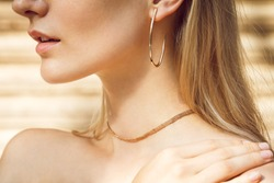 Close-up of a beautiful young blonde woman's neck without a shirt with gold earrings and a tiny gold choker.