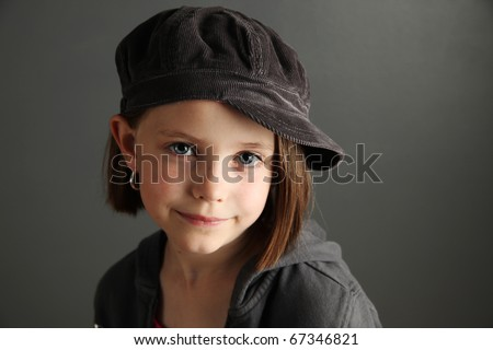 Close up of a beautiful young female child wearing a newsboy cap and hoop earrings
