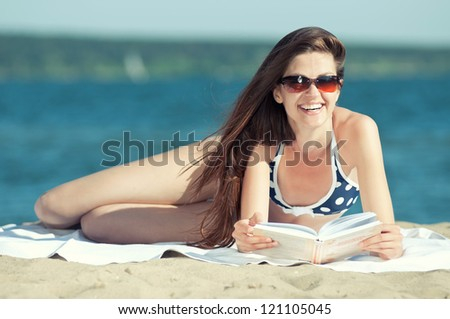 Close up of a beautiful young woman reading book on beach