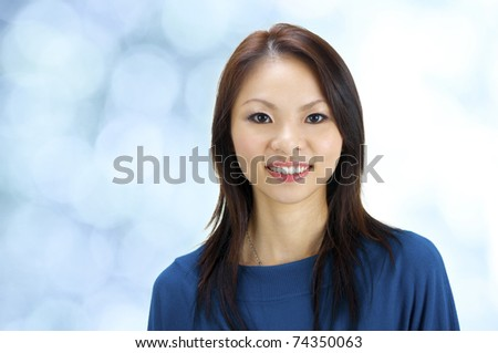 Close-up of a beautiful young woman smiling on blue background