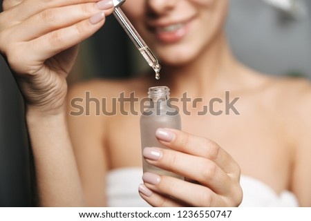 Close up of a beautiful young woman wrapped in towel applying cosmetic oil from a bottle on her face