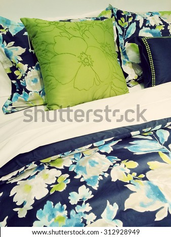 Close-up of a bed. Blue and green bed linen with floral design.