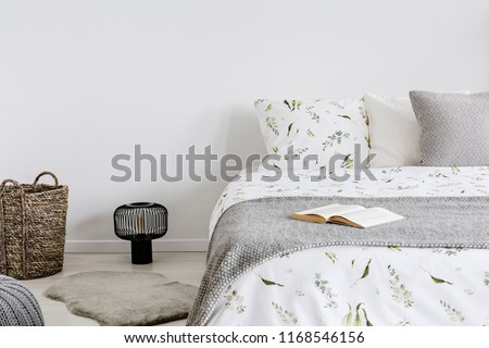 close-up of a bed with eco cotton and wool bedding and pillows in a bright bedroom interior. Real photo.