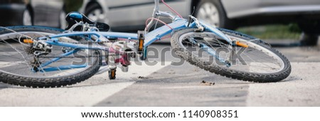 Close-up of a bicycle on an empty road crossing with cars in the background a dangerous car accident concept