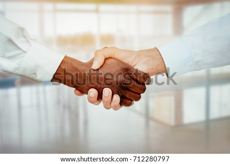 Shutterstock Close-up of a black and white hands shaking over a good business agreement.