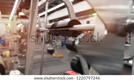 Close-up of a black foam pad for neck support in a modern gym without people. Modern gym interior with equipment. Vertical weight lifting element. #1220797246