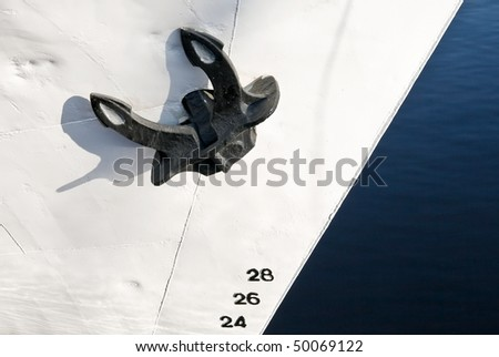 Close up of a black ship's mooring anchor on white painted bow with draft scale numbering - stock photo
