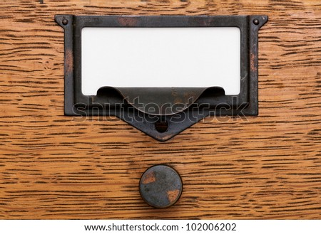 Close up of a blank, white label in a grungy, tarnished brass label holder and drawer pull on an oak filing cabinet drawer. - stock photo