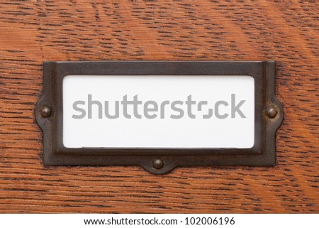 Close up of a blank, white label in an old brass label holder on an oak filing cabinet drawer.