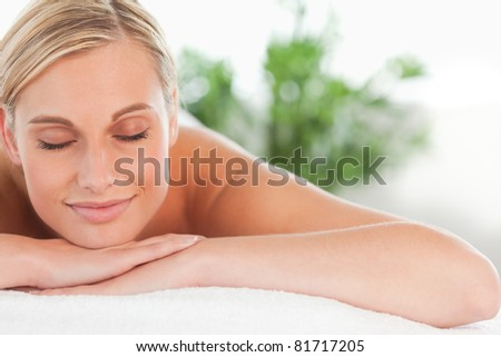 Close up of a blonde smiling woman relaxing on a lounger with eyes closed in a wellness center