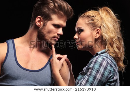 Close up of a blonde woman holding her boyfriend chin with he finger, looking at each other. On black background.