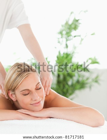 Close up of a blonde woman relaxing on a lounger enjoys a massage in a wellness center