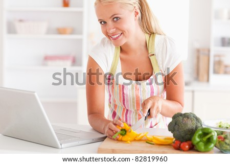 Close up of a blonde woman using a laptop to cook in her kitchen