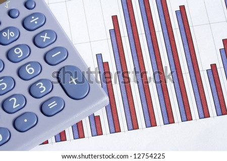 Close up of a blue calculator next to a red and blue bar chart on a white background